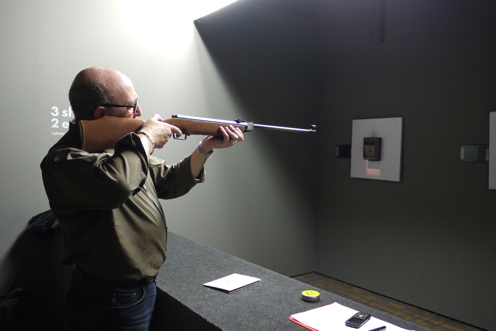 Ein Mann am Jahrmarkt-Schiessbudenstand zielt mit dem Gewehr
