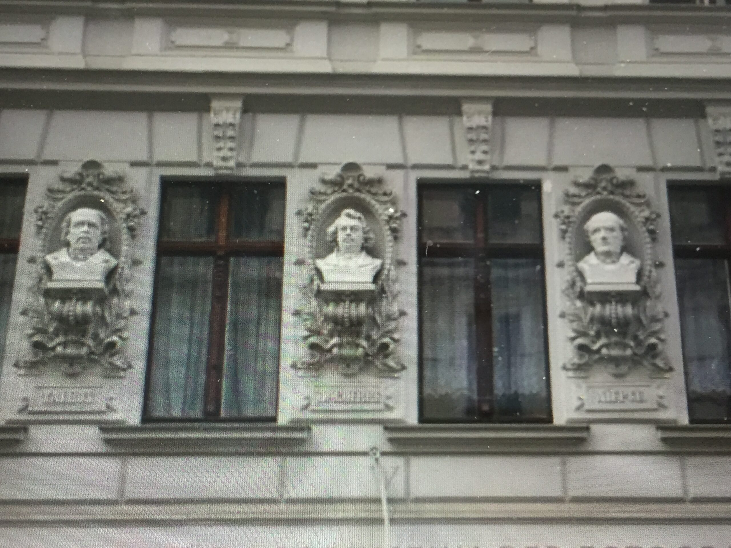 Drei Gipsbüsten an einer Hausfassade, es sind die drei grossen Fotopioniere