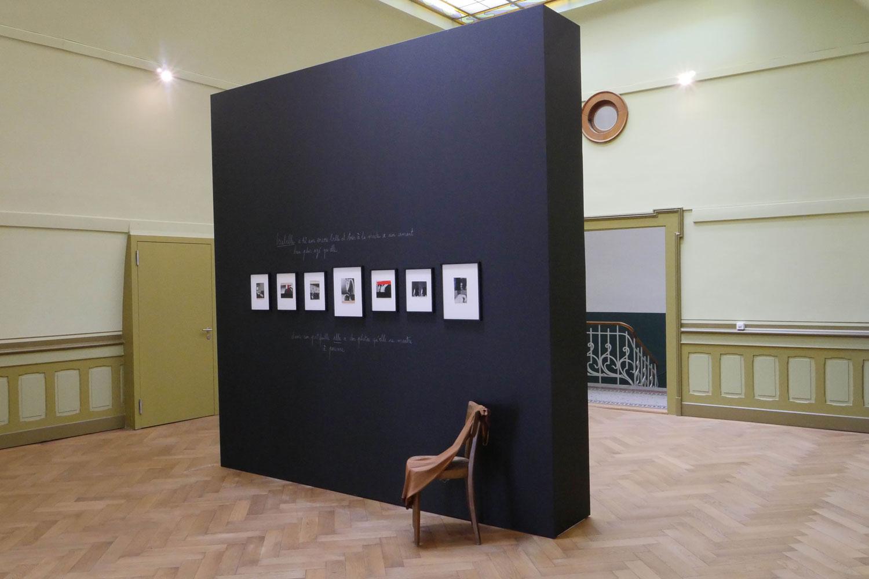 Eine schwarze Wand, auf der sieben Fotografien hängen