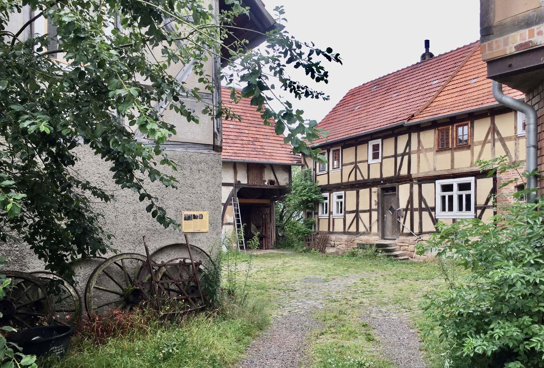Ein Bauernhof. An einer Hauswand eine Fototafel mit Text