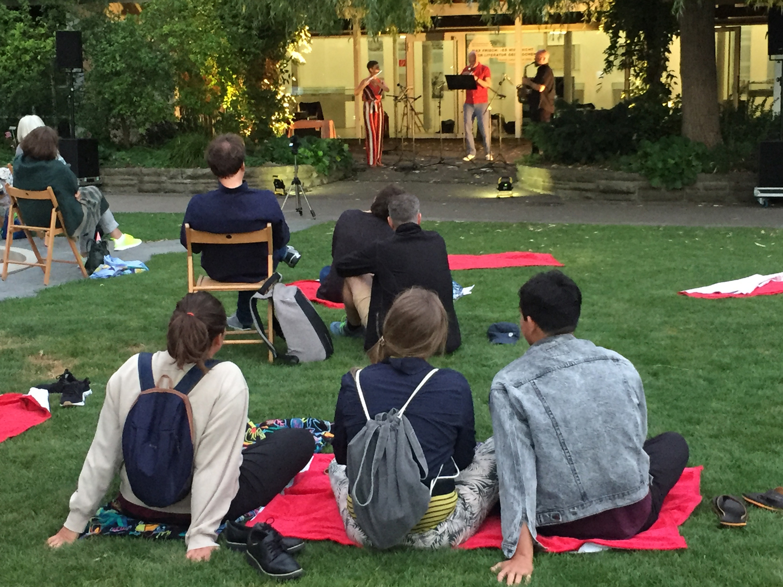 Menschen hören bei einem Openair Konzert zeitgenössische E-Musik