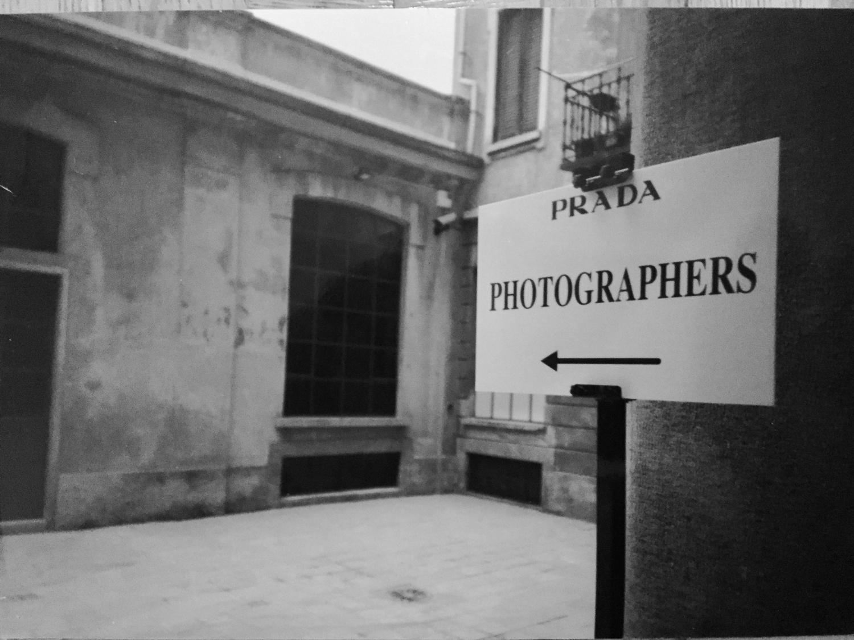 Im Hof der Modefirma Prada in Mailand steht eine Tafel, die anzeigt, wo sich die Modefotografen einfinden sollen