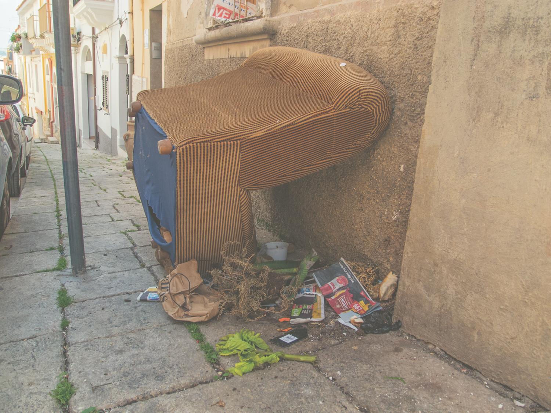 Ein umgekipptes Sofa und Abfallgegenstände daneben