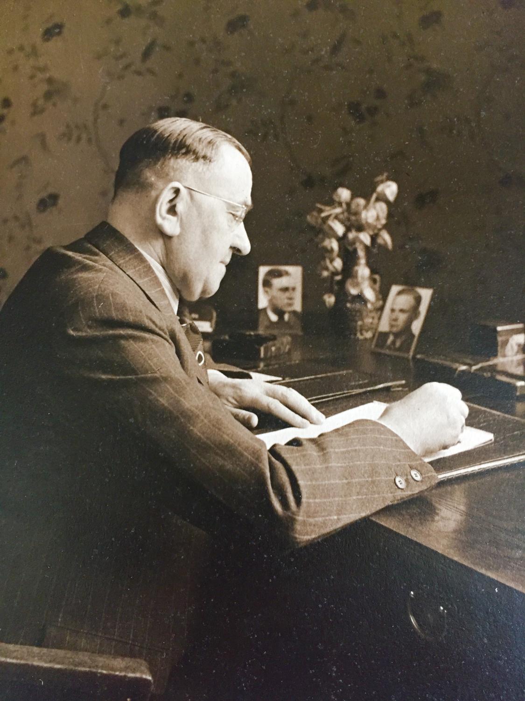 Ein älterer Herr sitzt am Schreibtisch, vor ihm liegt ein Blatt Papier