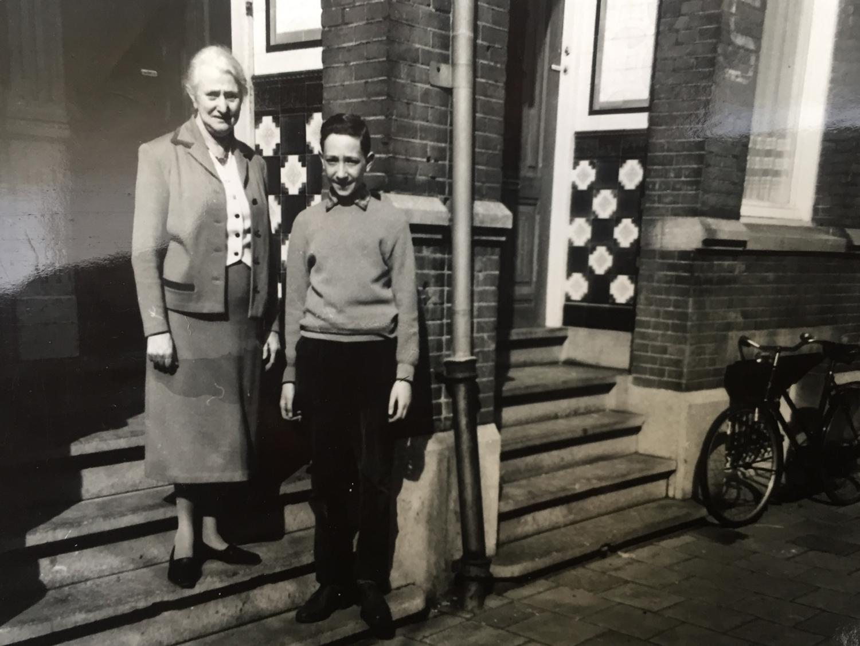 Ein Junge und eine ältere Dame stehen auf der Treppe eines Hauseingangs