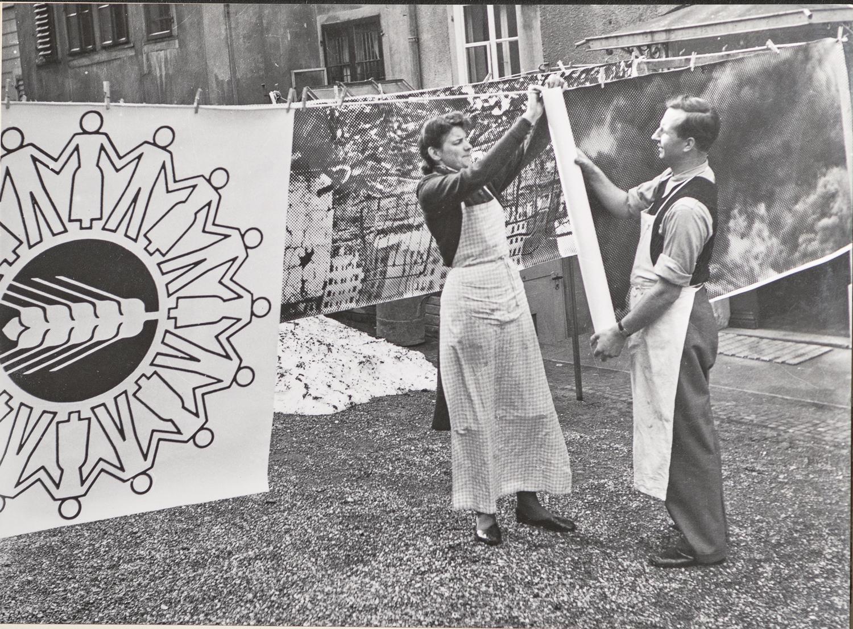 Luzzi und Michael Wolgensinger hängen eine leintuchgrosse Fotografie zum Trocknen auf einer Wäscheleine auf